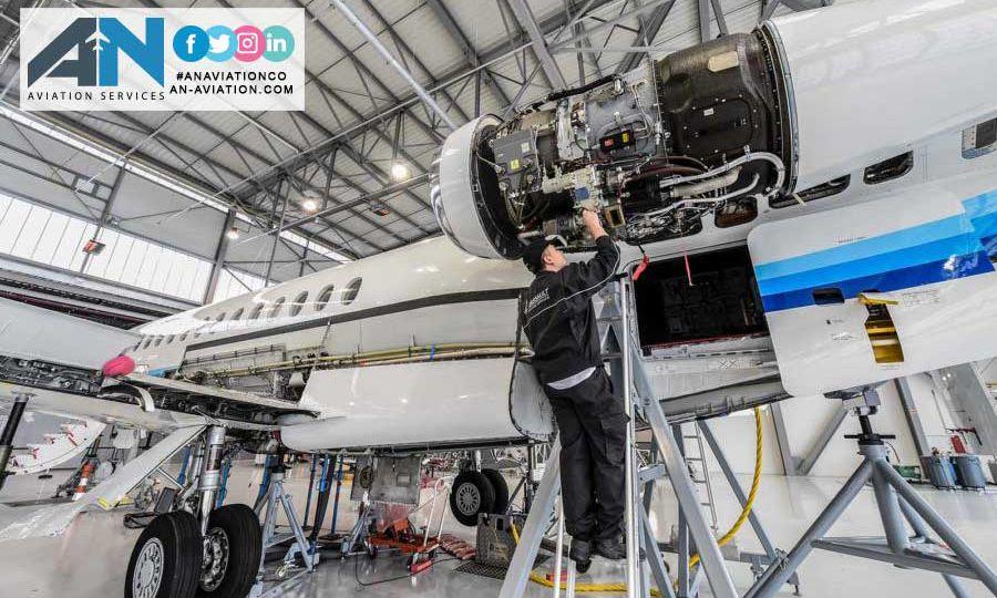 AN AIRCRAFT MECHANIC IS CHECKING AN ENGIN